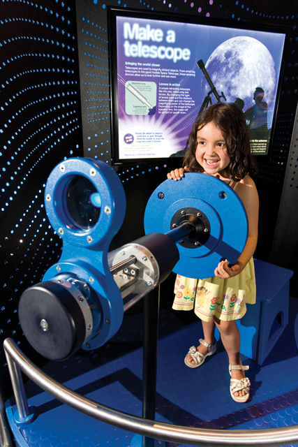Little girl in Scitech science exhibit turning a blue wheel on a telescope.