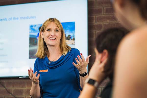 woman presenting to a group, her hands are up and she looks engaged