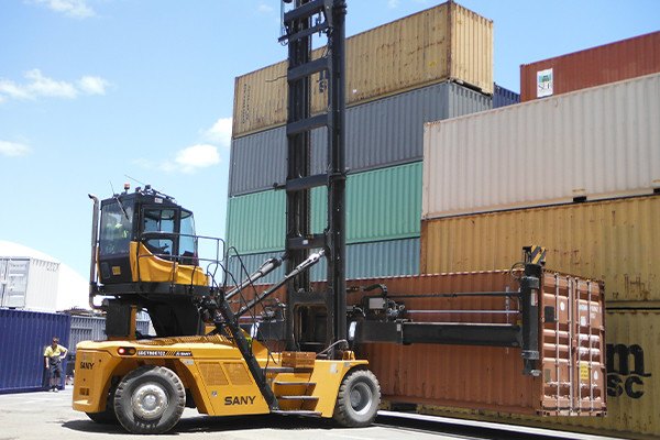Forklift lifting shipping container in shipping container yard