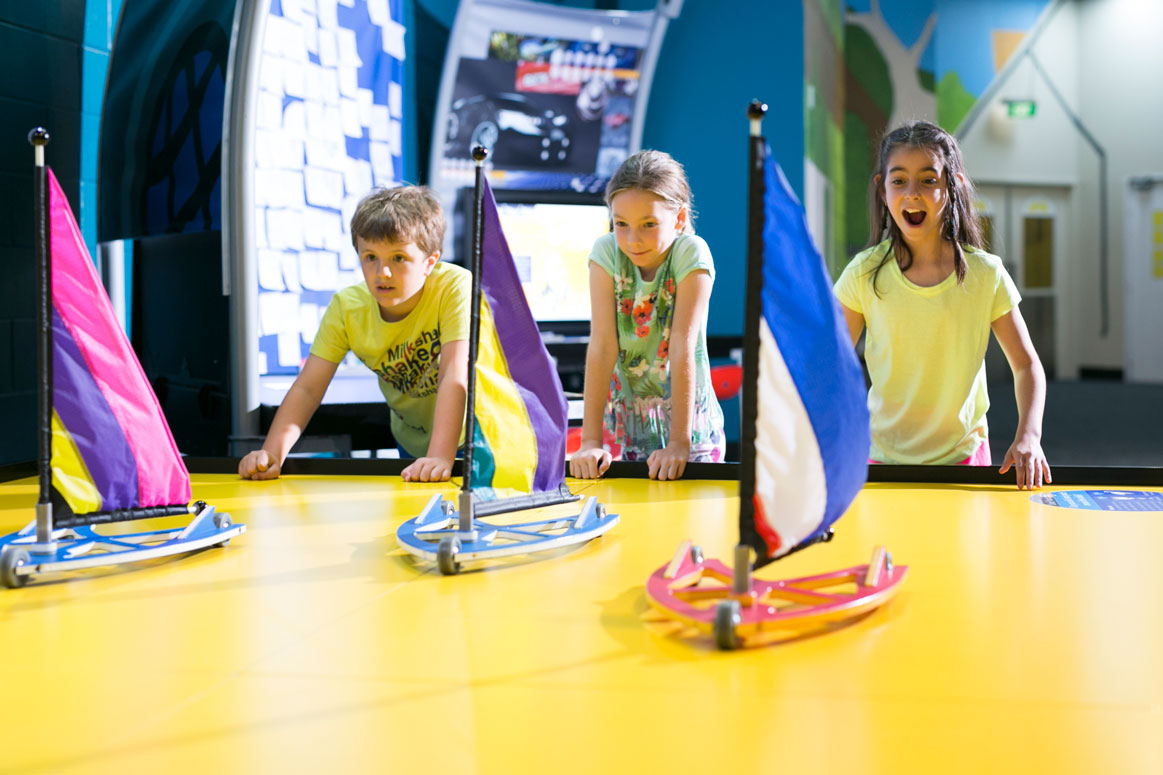 Three children racing land yachts across a table in the Going Places exhibition at Scitech.