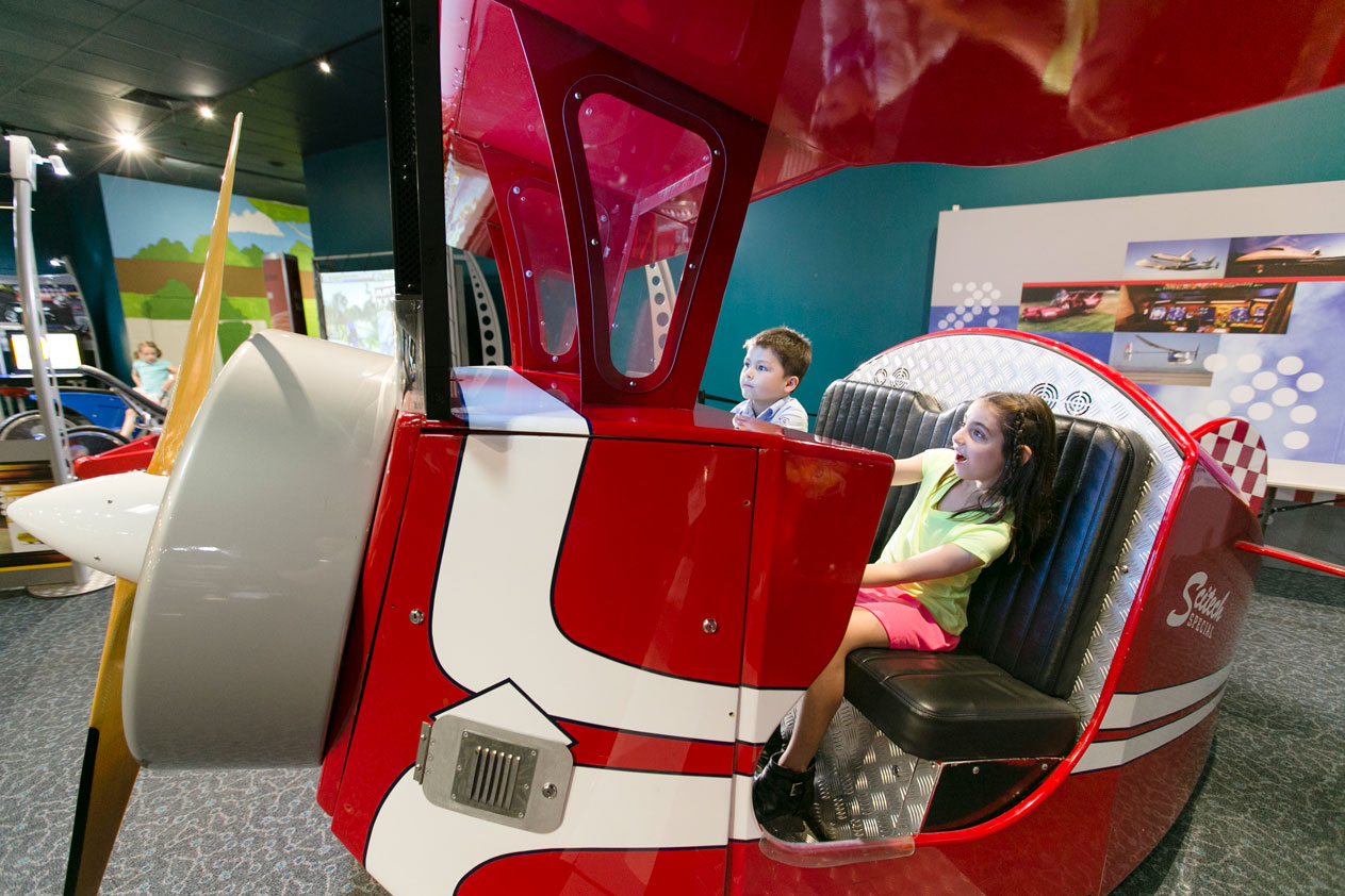Two young children operating the flight simulator exhibit at Scitech's Going Places.