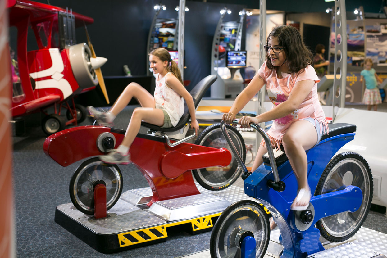 Two teenage girls riding exercise bike models against each other for the Going Places exhibition.