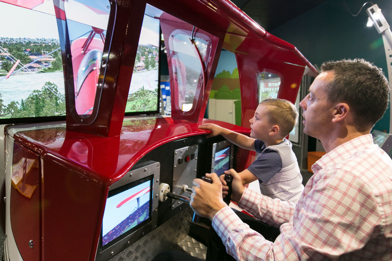 A young boy and father flying a plane in the flight simulator for Going Places Exhibition.