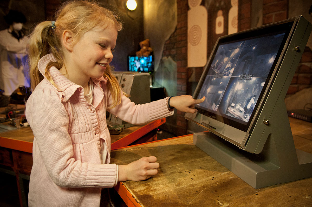 A young girl points to a computer screen showing 4 security camera angles.