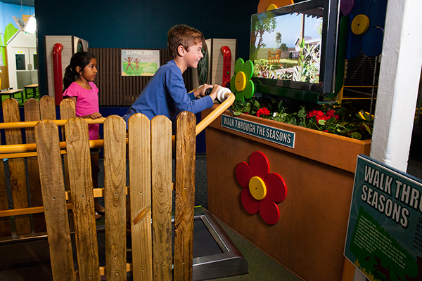 A young boy walking on a treadmill watching a seasons simulator on a screen.