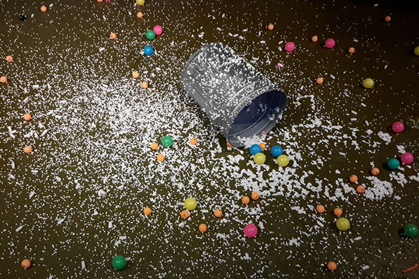 A empty metal bucket on the floor covered in white confetti and coloured bouncy balls.