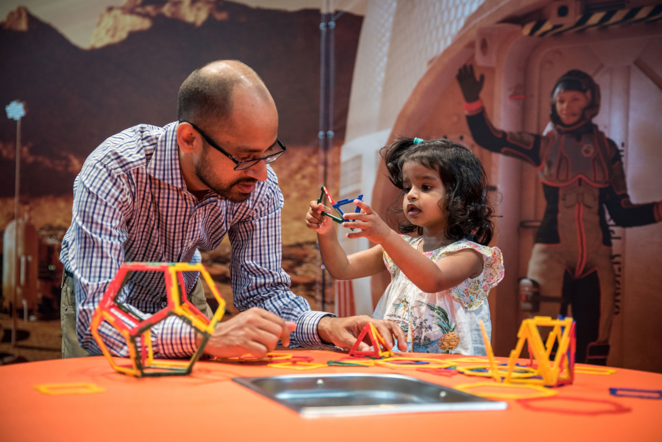 Little girl playing with plastic block toys with her father, a woman in a slim astronaut suit is gesturing behind them.