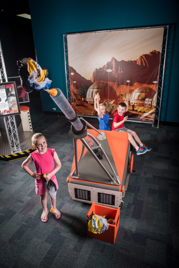 Three young children shooting off a canon in a Scitech exhibit.