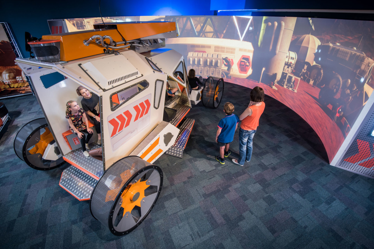 Some children playing in a simulation and large scale model of a mars rover in the Scitech Exhibition Space.