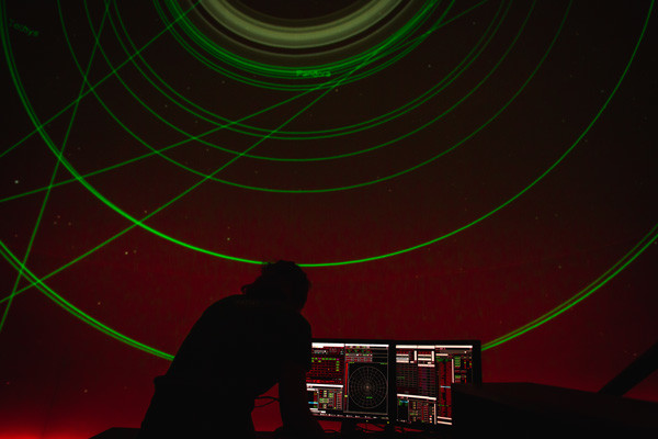 A planetarium presenter standing at the computer in front of the screen, showing a laser light show.