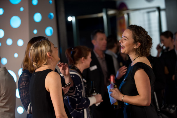 Two women laughing in casual conversation and a private event.