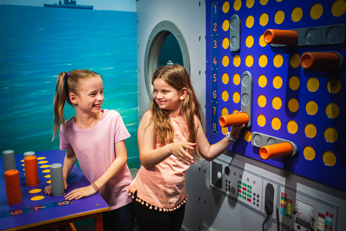 Two girls smiling at eachother while playing a life size game of battleships