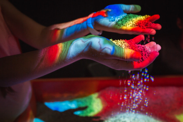 A pair of hands letting sand sift through their fingers with coloured gradients of light on top.