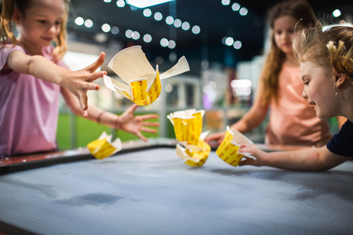 Three girls playing with paper cups that are floating in wind power.