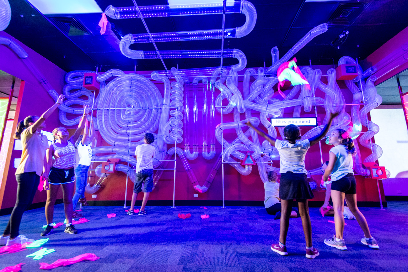 A group of children playing in a UV lit up space, the Kaartdjin Koorliny Gallery.