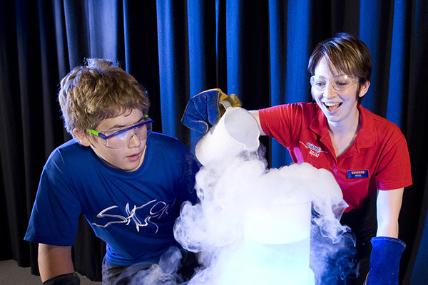 A young woman pouring dry ice into a beaker, a young boy looks on with interest.