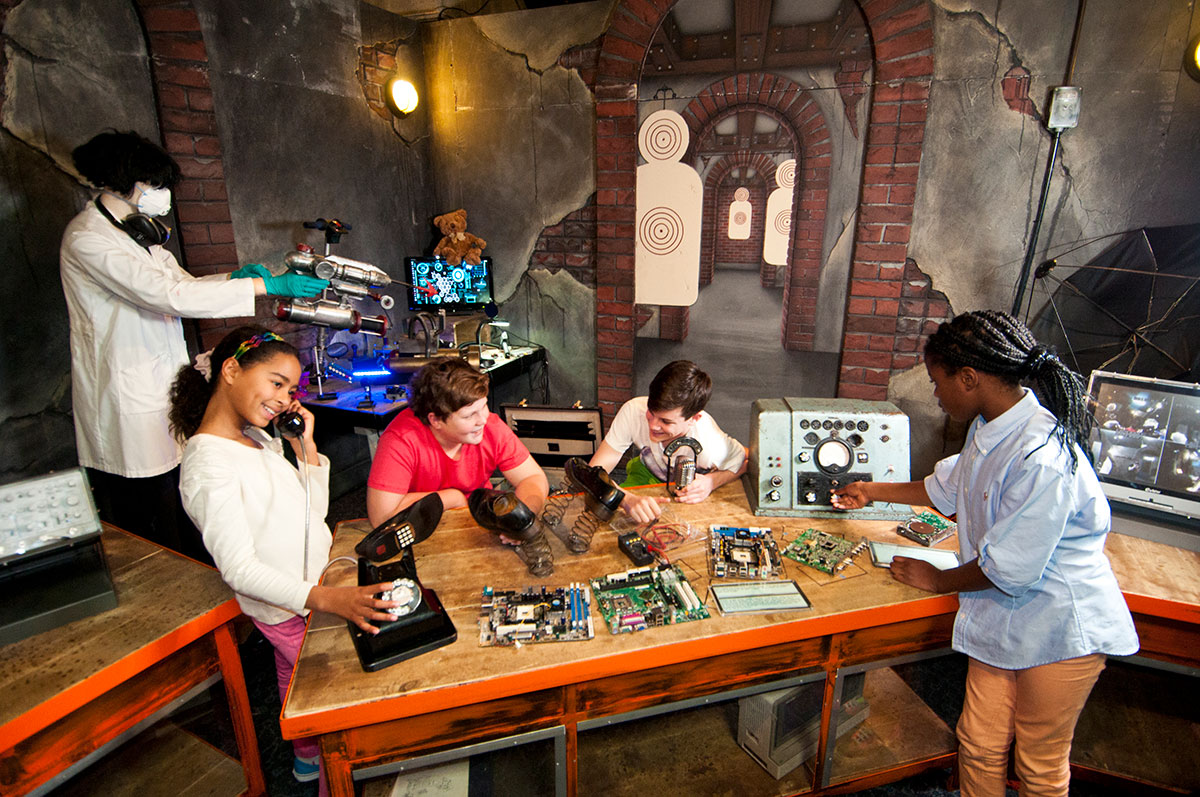 A group of children in a workshop interacting with various spy equipment objects.
