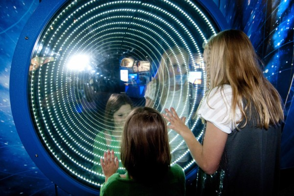 A young girl and a teenage girl looking at a digital wall simulating a black hole.