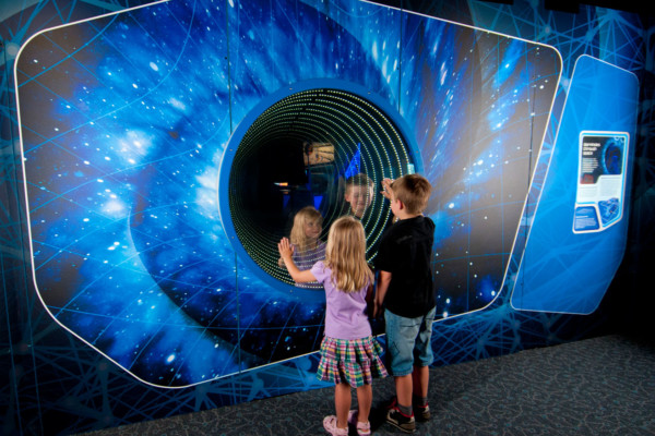Two young children playing infront of a worm hole simulator in the Science Fiction Science Future Exhibition.
