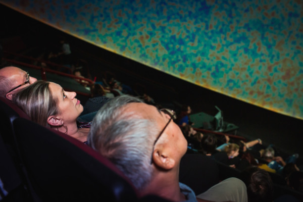 Three adults sitting in the planetarium theater, watching show.
