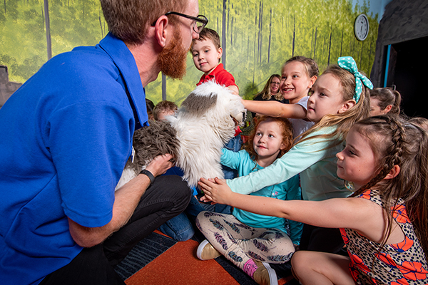 A man holding a dog hand puppet for a group of children to pat.