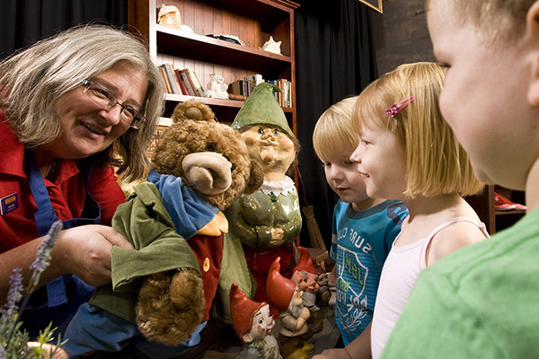 A woman holding a bear hand puppet to three young children