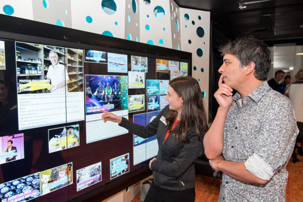 Two adults looking at a science information wall at Scitech Alumni event