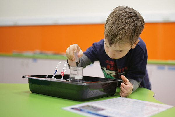 A small boy playing with a pipette and water in a science lab.