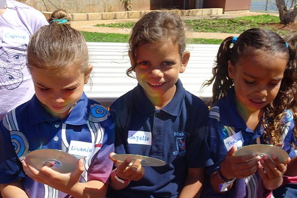 Three young school children holding cds from the AEP program