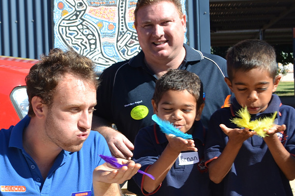 A Scitech science presenter with two young boys blowing feathers from their hands
