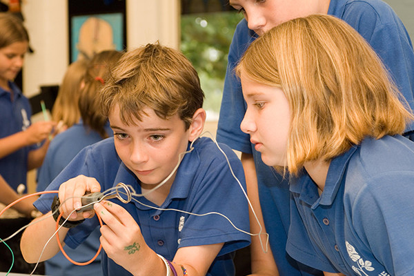 Two school children looking at a metal string object in awe during a Scitech Science workshop