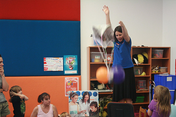 A Scitech science presenter dropping a balloon toy from a height at a library