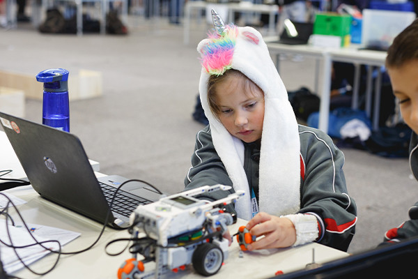 Child wearing unicorn beanie playing with robotics toy in a workshop at Scitech.