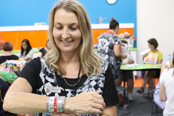 Middle aged woman putting on a wristband in a teacher's workshop.