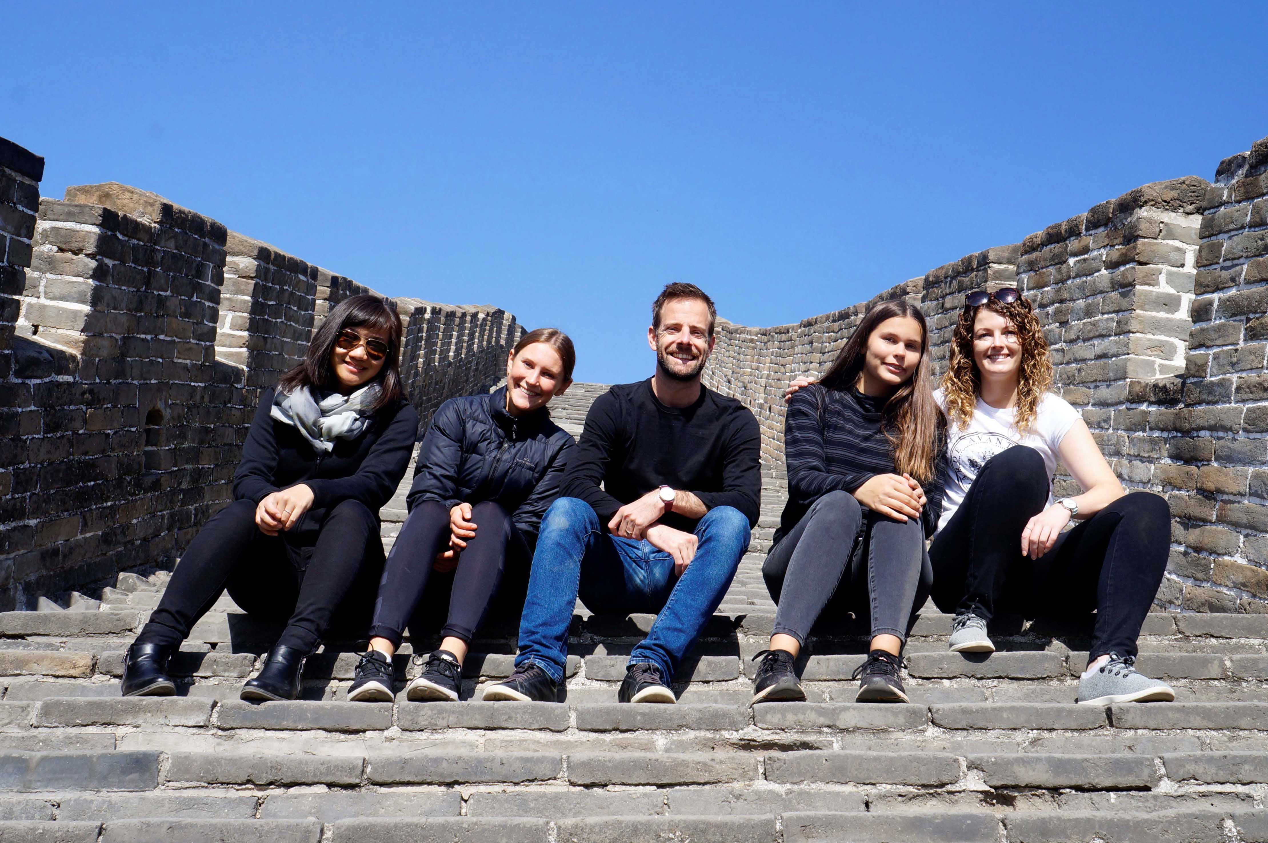 Five smiling adults sitting on a cement staircase on a sunny day in China from the Beijing Bound program
