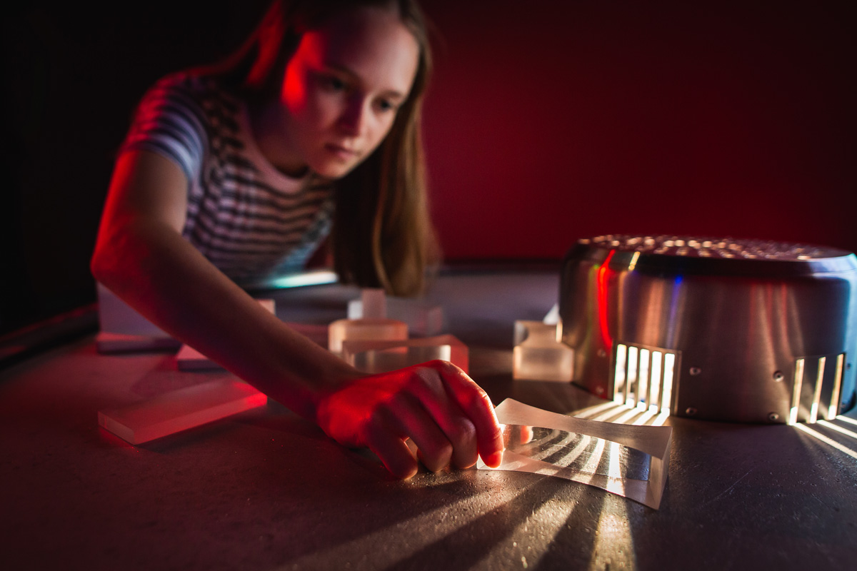 A young girl plays with optical components such as prisms and lenses.