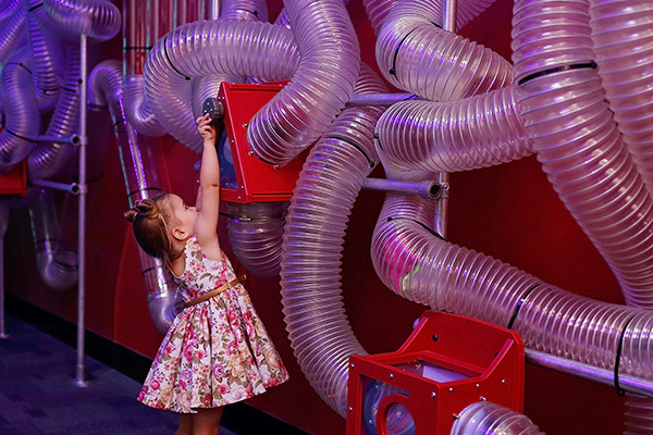 A girl playing in the Kaartadjin Koorliny gallery at Scitech, she is standing in front of plastic tubing.