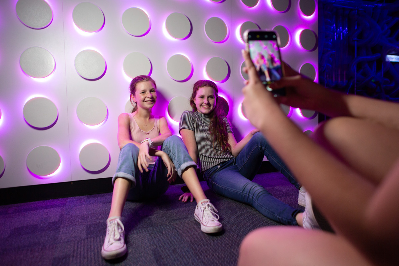 Two girls sitting on the ground in front of the Kaartadjin Koorliny wall at Scitech having their photo taken