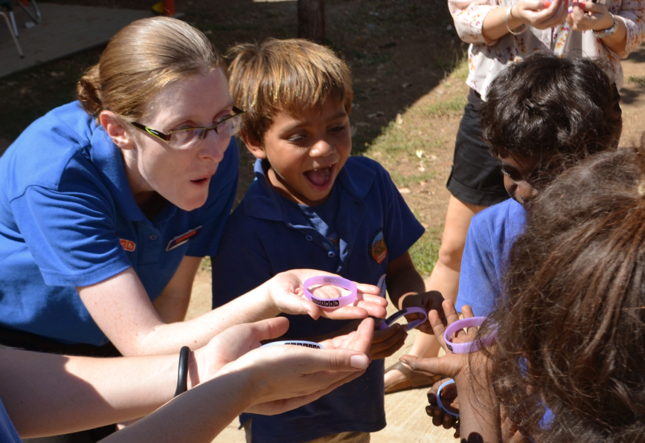 Scitech science presenter with young children holding scitech branded wristbands