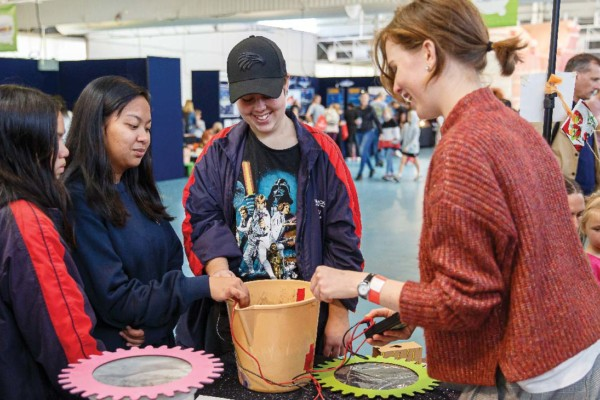 A group of teenagers engaging in a science activity at a science fair.