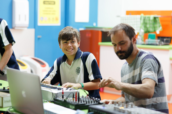 An adult and teenage boy playing with sound mixing equipment