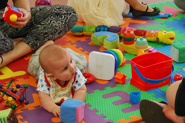 A baby on a playmat surrounded by toys