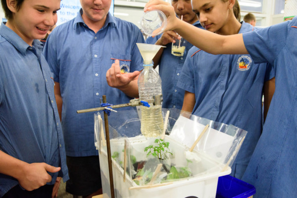 A group of school kids pouring water into a water bottle over a small plant garden
