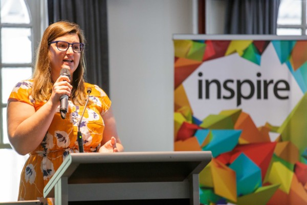 A smart casual woman giving a presentation at an event called Inspire