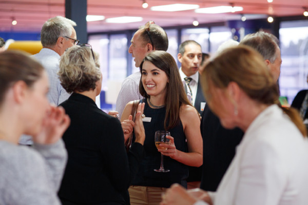 A group of people mingling at a corporate function, some holding glasses of wine.