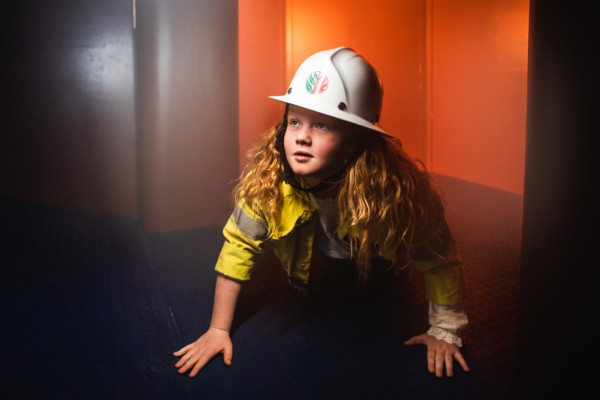 A young girl wearing a firefighters uniform and hard hat crouching on all fours.