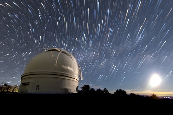 Time lapse of starry night sky above a planetarium.