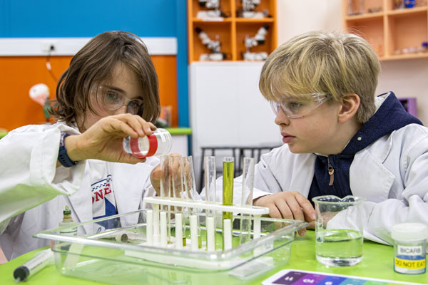 Two students pouring liquids into test tubes.