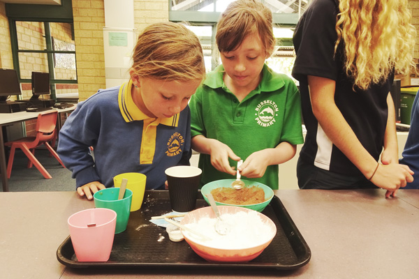 Two young children combine materials in a bowl.