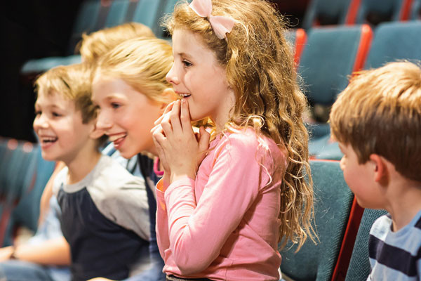 A group of students laughing and watching a science show.